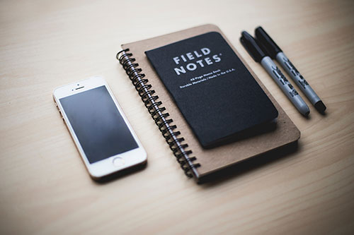 Picture of a phone, notebooks & pens